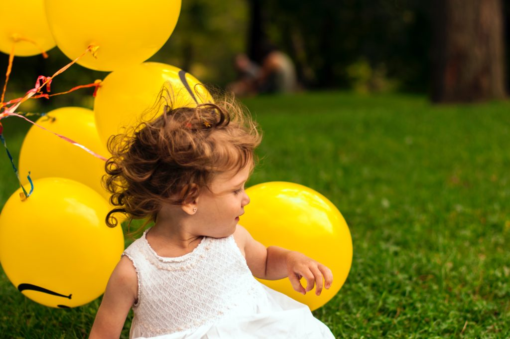 girl sitting on grass near balloon